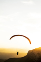 Paraglider flying, mountains in the background during sunset - ACPF00314