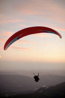 Paraglider flying with mountains in the background during sunset - ACPF00317