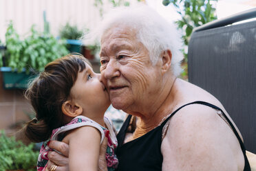 Baby girl kissing her grandmother on terrace - GEMF02376