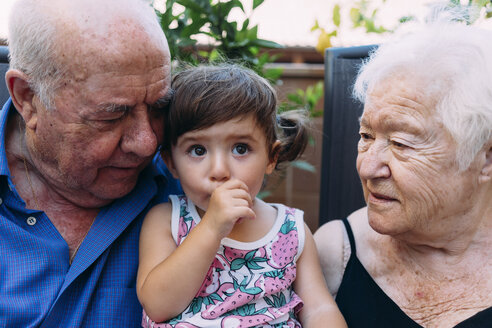 Grandparents looking at baby girl sucking thumb - GEMF02382