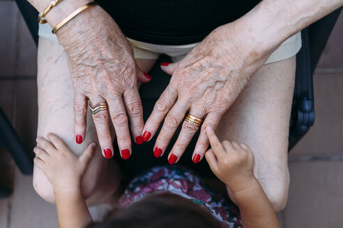 Hand of baby girl pointing on hand of senior woman with rings and red painted nails - GEMF02385