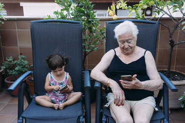 Grandmother and baby girl sitting side by side on the terrace using mobile phones - GEMF02391