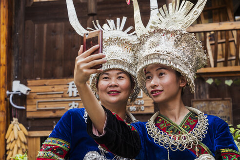 China, Guizhou, two Miao women wearing traditional dresses and headdresses taking a selfie with smartphone - KKAF01634