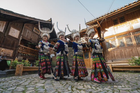 China, Guizhou, Miao women wearing traditional dresses and headdresses posing on village square - KKAF01646