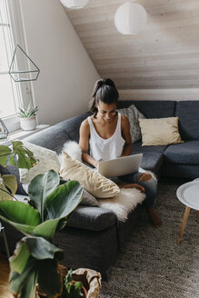 Smiling young woman sitting on the couch at home using laptop - LHPF00005