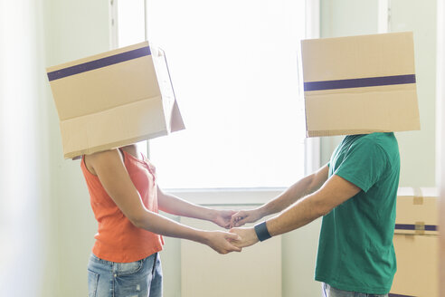 Couple with heads in cardboard boxes holding hands - FBAF00014
