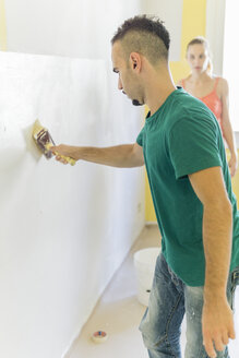 Man painting wall at new home while his girl friend watching him - FBAF00032