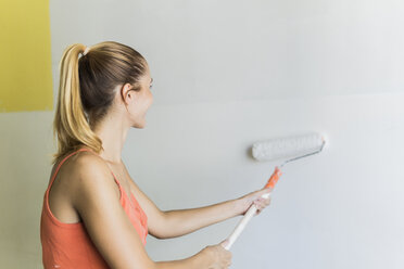 Young woman painting wall at new home - FBAF00035