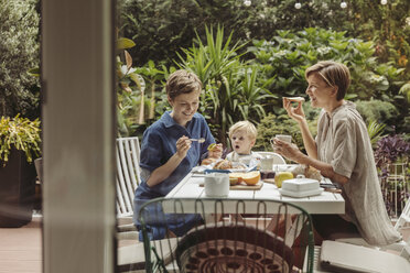 Two happy mothers at breakfast table outdoors with their child - MFF04416