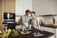 Happy lesbian couple in kitchen cooking together - MFF04422