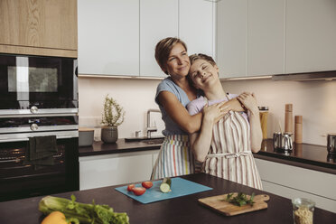 Happy lesbian couple standing in kitchen with aprons - MFF04428