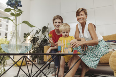 Portrait of two mothers learning and playing with their child at home - MFF04431