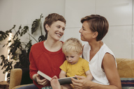 Two mothers reading a book with their child at home - MFF04434