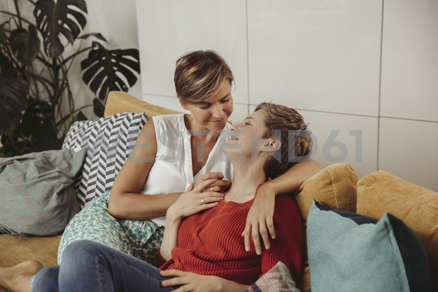 Happy lesbian couple cuddling on couch - MFF04437 - Mareen Fischinger/Westend61