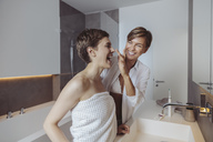 Happy lesbian couple getting ready for their day in the bathroom - MFF04452