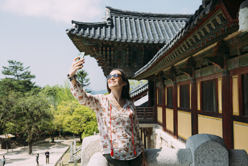 South Korea, Gyeongju, happy woman taking a selfie with cell phone in Bulguksa Temple - GEMF02395