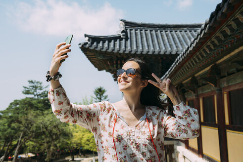 South Korea, Gyeongju, happy woman taking a selfie with cell phone in Bulguksa Temple - GEMF02398
