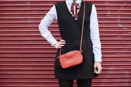 Fashionable woman with red handbag wearing black dress standing in front of red roller shutter - IGGF00528