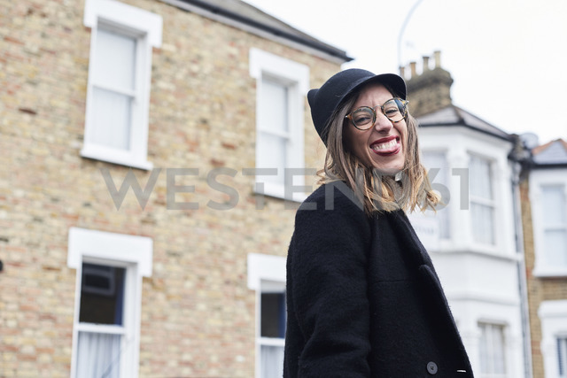 Portrait of woman dressed in black sticking out tongue - IGGF00531