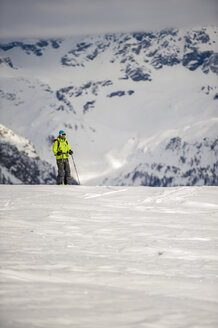 Skier stands on the edge of a steep slope in Devero Valley with snowy mountains in background on a cloudy day. Baceno, Piemonte, Ossola. - AURF03539