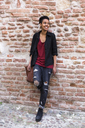 Portrait of smiling young woman leaning against brick wall - GIOF04259