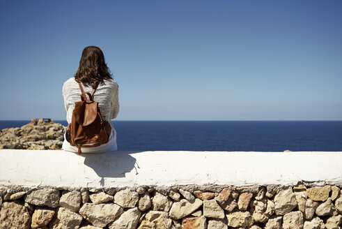 Young brunette woman sitting on wall, looking at view - IGGF00543