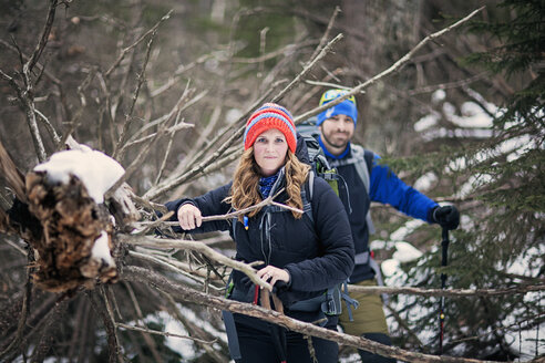 A couple poses for a portrait while winter hiking in the woods. - AURF03550