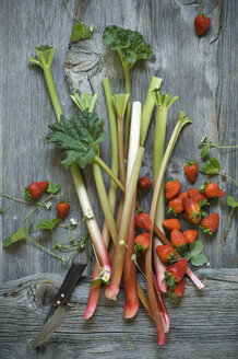 Rhubarb stalks and strawberries on wood - ASF06227