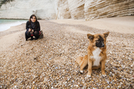Italy, Vieste, stray dog sitting on Vignanotica Beach while smiling woman crouching in the background - FLMF00008