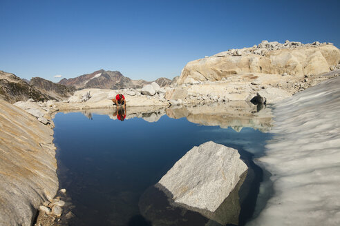 A hiker stops to drink from a glacier fed alpine tarn near Whistler, British Columbia, Canada. - AURF03695