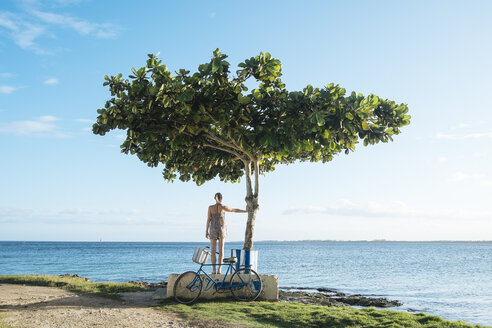 A girl stands with her bike next to a tree in Playa Larga, Cuba - AURF03707