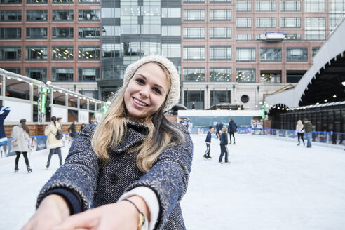 Blond young woman having fun ice skating, holding hands of young man - IGGF00547
