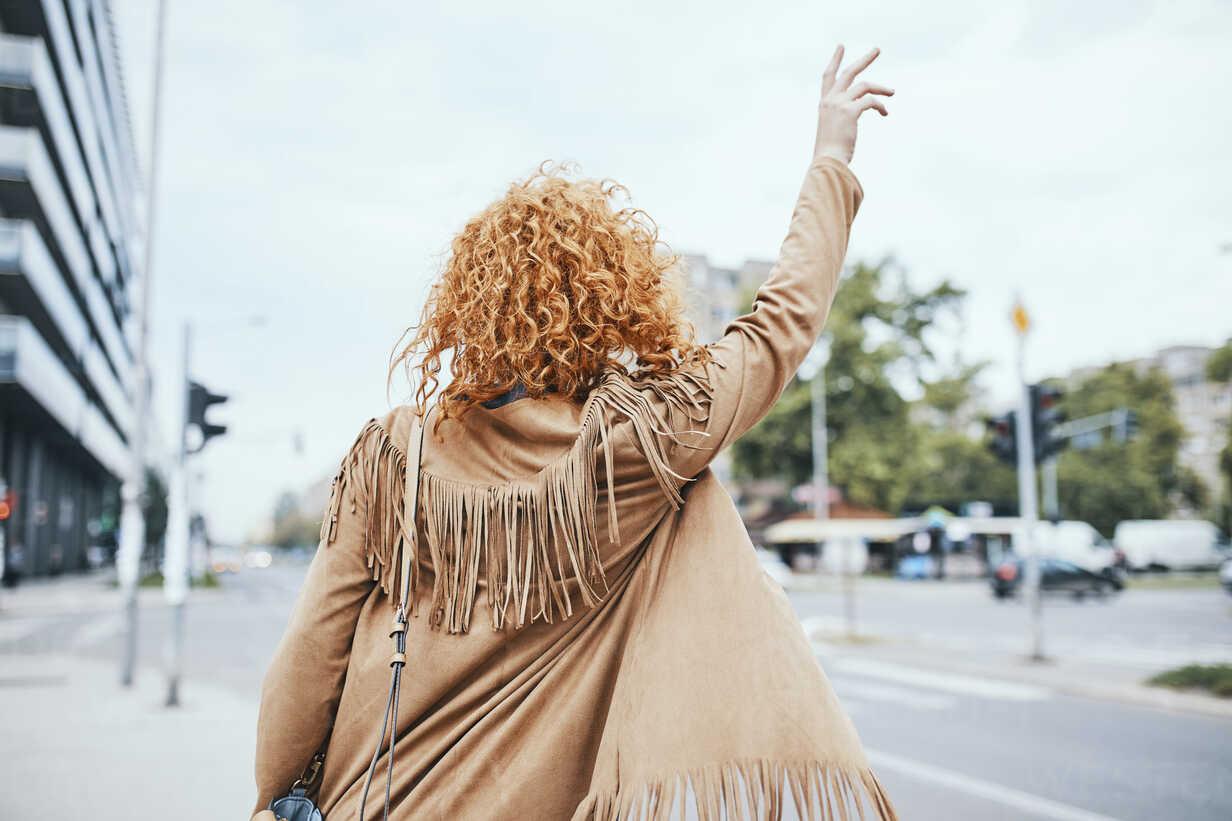 Redheaded woman hailing a taxi in the street - ZEDF01502 - Zeljko Dangubic/Westend61