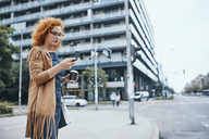 Young woman waiting to cross road, using smartphone - ZEDF01514