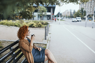 Young woman sitting on a bench, drinking coffee - ZEDF01517