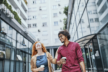 Colleagues walking together in the city, woman drinking coffee - ZEDF01520