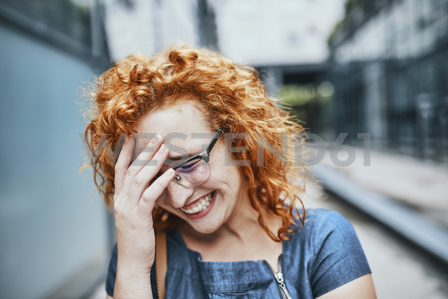 Portrait of a young redheaded woman wearing glasses, smiling - ZEDF01529