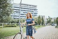 Young woman walking in park, pushing bicycle - ZEDF01535