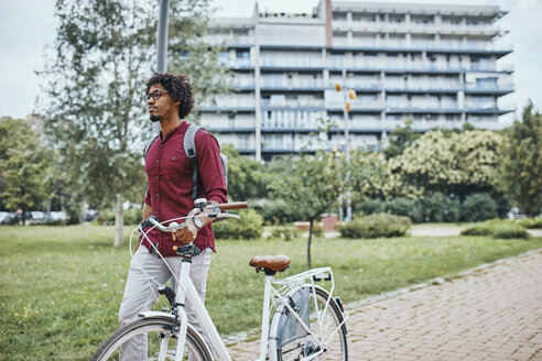 Young man with backpack pushing bicycle in park - ZEDF01538