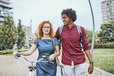 Friends walking in park, talking, woman pushing bicycle - ZEDF01541