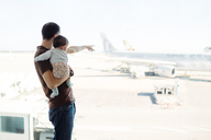 Spain, Barcelona, Man holding a baby girl at the airport pointing at the airplanes - GEMF02399