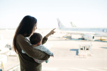 Mother holding a baby girl at the airport, pointing at the airplanes - GEMF02402