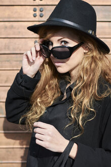 Mid adult woman wearing black hat and sunglasses - IGGF00559