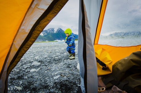 A warmly dressed two year old boy explores outside a tent on a rocky beach next to Bear Lake, Kenai Fjords National Park, Alaska. - AURF03727
