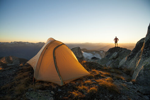 A silhouetted hiker stands on a rock bluff while camping on Saxifrage Peak, Pemberton, BC, Canada. - AURF03748