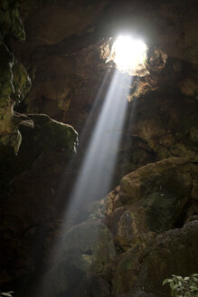 A ray of sun light enters the Calcehtok Mayan caves near Oxkintok in Yucatan Peninsula, Mexico. These caves are where for the ancient Mayans an entrance to Xibalba, the underworld. - AURF03787