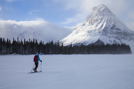 A woman skiing on Two Medicine Lake in front of Sinopah Mountain and Painted Tepee Peak in Glacier National Park, Montana. - AURF03799