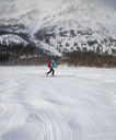A woman skis on wind patterned snow at Two Medicine Lake, Glacier National Park, Montana. - AURF03802