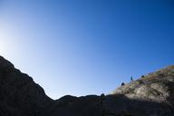 A young man runs among glacial erratics above Spectacle Lakes, Rocky Mountain National Park, Colorado. - AURF03856