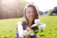 Portrait of smiling young woman in a park holding flowers - GIOF04282
